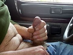 I like to jerk off in public. This time I'm in a parking lot. If you listen close there is a car passing behind me just after I cum