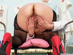 Tasty looking voluptuous granny Stazka widens her red-haired pussy with hands while sitting in the gynecological chair in steamy sex clip by Naughty Head Nurse.