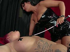 Jasmine Black is a kinky lesbian mistress that loves her slaves big breasts. Red-haired tattooed slave woman in tiny black thong gets he juggs eaten by kinky latex-clad domina.