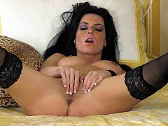 Dark haired and cute brunette in black stockings is masturbating her shaved pussy indoors