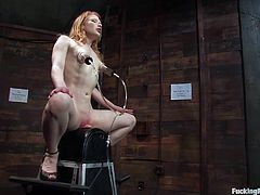 Get a load of this bondage scene where a horny redhead has a great time being fucked by a machine after being tortured with clothes pins.