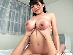 Stunning Japanese girl with very big tits gives a blowjob. After that she lies down on a bed and gets her hairy pussy fucked.