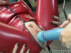 Two lesbian babes, Karina Currie and Karlie Simon in latex are using a dildo with it in her mouth and then vibrating pussy of the babe in her red latex outfit. She's vibrating that slick slit til she cums.
