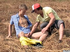 A twink is walking down the street when he sees a path. He walks down the path and sees another twink in the middle of the field jacking of. He offers to sucks his cock. They have gay sex and cum all over each other.
