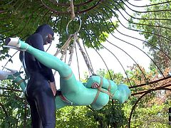 Latex Lucy is helpless outdoors in suspension bondage. She gets her mouth and vagina fucked by mistress in rubber outfit. Watch her get strapon fucked with no mercy in the garden.