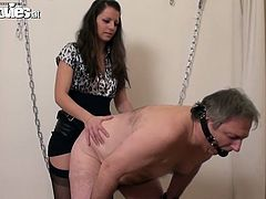 Dark-haired mistress Larissa Gold is having fun with some elderly dude. She ties him up to a wall and pounds his butt with a strap on.