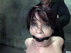 Sexy brunette girl gets tied up to a chair and toyed with a vibrator. After that the guy puts her in an aquarium filled with water and fingers her vagina.