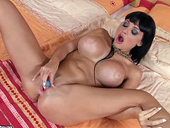 Sexy brunette Aletta Ocean demonstrates her well-shaped ass and big fake tits. Then she lies down on a bed and pleases herself with ardent fingering.