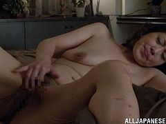 Chubby Japanese woman lies on a bed fingering her pussy. Then she sucks a cock and gets fucked doggystyle by younger guy.