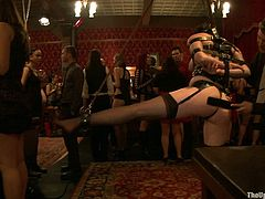 Have a look at this bondage scene where a slutty brunette is tortured and forced to suck on her master's big cock in front of many people.