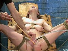 Blonde girl in glasses gets tied up and then the guy fixes lots of clothespins to her body. After that she gets fucked by a fucking machine and squirts.