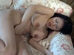 An orgasm craving Asian MILF plays with herself on the sofa after taking a shower fingering herself like crazy.