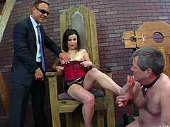 Veruca James is a dark haired domina in short skirt and shoes. She bars her natural tits and gets her feet licked by obedient naked slave man. She gives handjob to another guy at the same time.