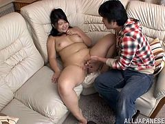 Fat Japanese chick with big boobs takes her clothes off and lies down on a sofa. She gets her pussy fingered by some guys.