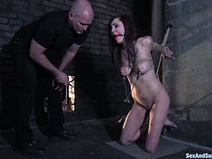 Cute brunette Princess Donna Dolore is having fun with Mark Davis in a basement. She lets the dude put her into a pillory and then sucks his dick and gets her delicious pussy pounded hard.