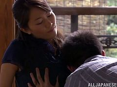 Stunning Asian MILF takes her clothes off and gets her hairy pussy licked. After that she sucks a cock standing on her knees and gets nailed.