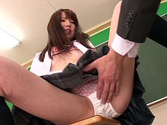 Pretty Japanese girl wearing a school uniform is having fun with a guy in a classroom. She caresses the man tenderly and then they have some naughty banging in cowgirl position.