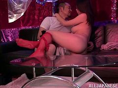 Beautiful Japanese stripper is performing a lap dance in a bar. She turns the man on and they bang right there on the sofa.