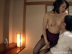 Sexy Japanese mom is having fun with some dude in the living room. She gets on her knees in front of him and plays with his dick till it explodes with cum.