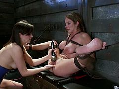 A busty girl is going to be fucked by a brunette who has an strapon dildo and takes advantage of the fact that the other girl is strapped with her legs opened.