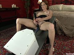 Horny chick on high heels lies on a sofa with her legs wide opened. She gets her hot vagina drilled by the fucking machine.