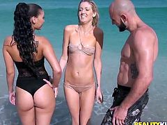 Two luscious babes (brunette and blond) hook up with a horny bald dude at they beach. They swim with him in the ocean wearing steamy bikini before he invites them over at his place.