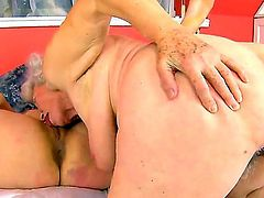 Black haired pretty babe Tess with arousing heavy make up and cheep slutty tattoos licks short haired blonde granny Norma with hanging tits and hairy cunt to wet orgasm.