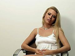 Young long haired blonde hottie Michelle Moist with heavy make up and natural boobies in sexy white dress remembers her lusty solo action during interview filmed in close up.