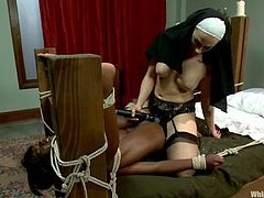 The kinkiest nun you've ever seen is going to dominate, tie and strapon fuck an ebony girl in this lesbian domination video.