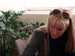 Young famous blonde pornstar Sophie Moone with long hair and sunglasses in average clothing gets filmed in point of view by her partner while opening present in living room.