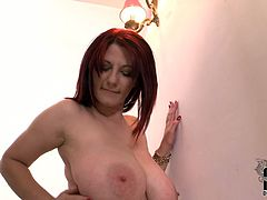 Redhead bitch with huge jugs is posing on cam naked. She is proud of her bust so she demonstrates her twins in all the glory. The boobs are so big so she can lick her own nipples. Check out this tricky video presented by DDF Network.