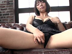 Sex hungry Japanese milf sits with legs spread aside in black lingerie tickling her cunt with mini vibrator before she stick her hand under panties to rub it intensively.