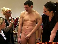 These clothed dominant females tease a man in their office by undressing him and playing with his erect penis.