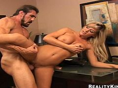 Well-endowed blonde Megan Monroe is getting naughty with some dude indoors. She gives him a blowjob and a handjob and then they bang in cowgirl position on a chair.
