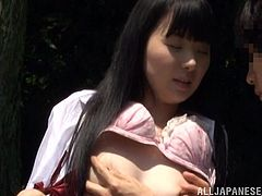 Nasty Japanese student is having fun with some guy in a forest. She pleases him with a blowjob and then they bang in cowgirl position on the ground.