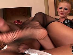 Torrid blond bitch with extra short hair almost bald hair style is filming in a steamy porn video. Wearing fishnet stockings she caresses hard dick with her soles.