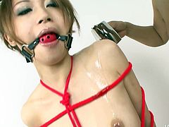 Playful Japanese chic in playful colorful bikini gets fully bandaged and her mouth plugged with a gag by perverse dude before he starts rubbing intensively her steamy body in sultry sex video by Jav HD.