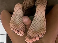 Tanned blond hottie in fishnet stockings provides a lucky dude with a footjob