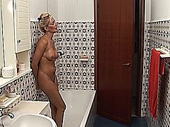 Magnificent blonde MILF is cleaning the house and takes a shower not knowing that her sons friend is watching her all the time with a stiff dick in his pants