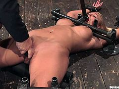 See the beautiful blonde Mellanie Monroe having her shaved pussy toyed while she's in a bondage device made especially to leave her immobile.