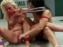Izamar Gutierrez and Tara Lynn Foxx fight in a ring. The blonde girl loses a battle, so she sucks a strap-on and gets her vagina toyed hard.