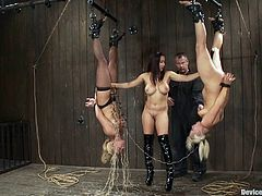 Isis Love is going to have a great time playing with two submissive blondes in this BDSM video where she hangs them upside down and toys their pussies.