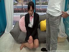 Petite Japanese office girl sits on a sofa in a studio. Some nude guy comes up to her and takes his dick out of his pants. Then he starts to masturbate looking at her.