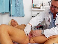 Curvaceous blond MILF has got saggy boobs. She stands tall totally naked in front of perverted doctor. He measures her body. Then she lies on a couch spreading her legs wide. Old pervert opens pussy folds showing the cave close-up.