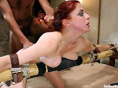 Penny Pax gets tied to the edge of the bed with her arms spread across a giant post. Her tits are squished and her master, Mickey Mod, shoves his big black dick into her mouth. She takes the whole thing down. He fucks her from behind, too. He grabs her mouth as he is pounding her very hard.