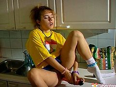 This gal in loose yellow T-shirt gets tired of washing the dishes. Palatable cutie with sweet tits and nice rounded butt spreads legs on the kitchen counter and starts polishing her wet pussy with a pink dildo right away.