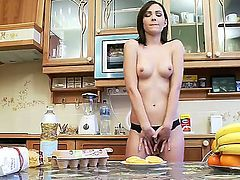 Sweet babe Nikita performs a naughty striptease before laying down on a kitchen table and teasing her snatch with a slice of an orange while masturbating.