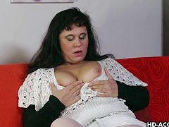 This dark haired, chubby mature woman has a nice pair of boobs. She pulls them out and plays with them a bit. Then she spreads her pussy lip and starts to masturbate. After that, she calls over her younger male friend and he puts his cock in her mouth and in her cunt.