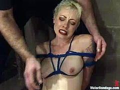 Hot blonde Lorelei Leeis having fun with a guy called Torque in a cellar. The man binds the girl and then slams her vag with a dildo and drowns her in a glass box.