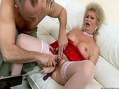Trashy granny with massive make-up on is looking cheesy wearing white nylon stockings and red tight corset. Ugly mature slut lies on a couch with her legs wide open letting the guy finger her clam. She moans with pleasure.